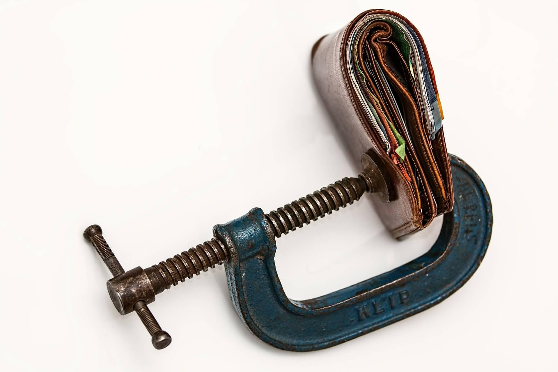 Wallet in clamp. Public domain: http://pixabay.com/en/purse-money-credit-squeeze-wallet-522622/
